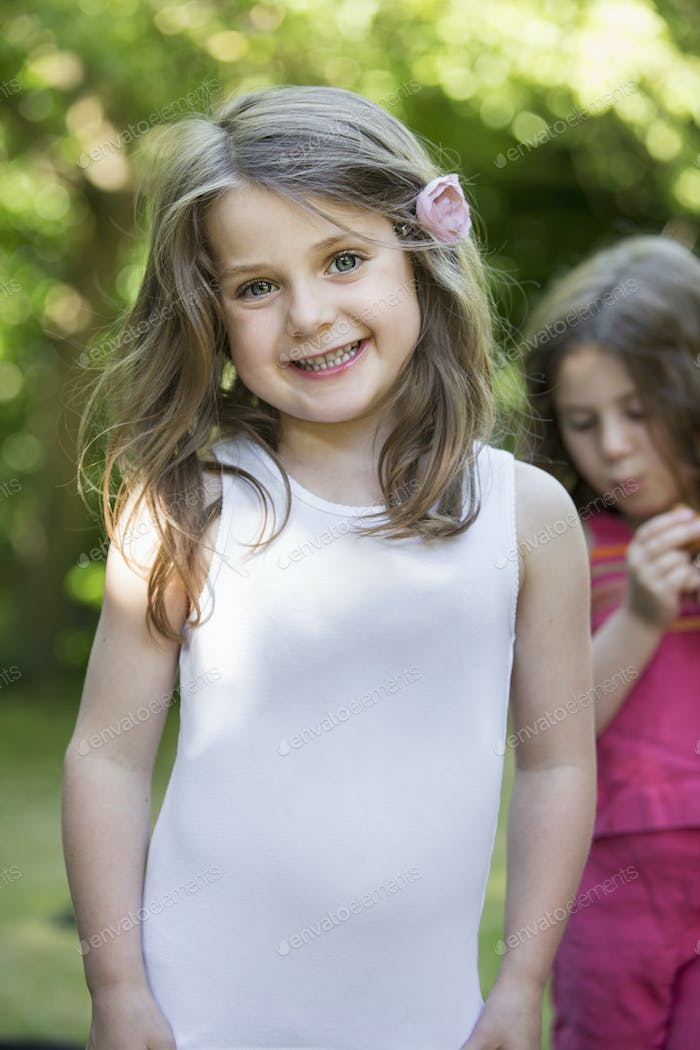 Two smiling young girls at a garden party.