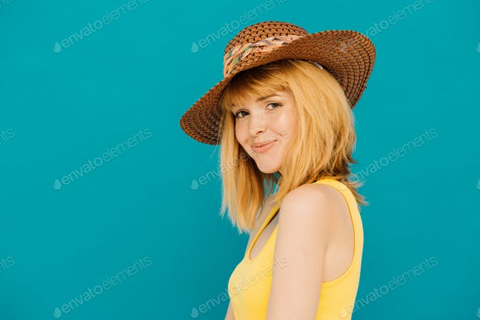 Beautiful emotional woman with hat. Blue color background.