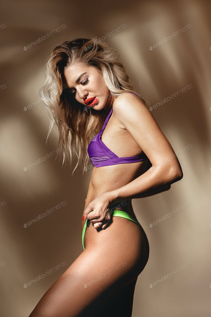 Slender sexy girl with red lipstick dressed in acid yellow and purple swimsuit is posing against a