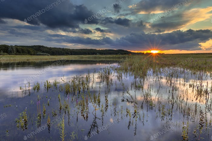 Dark river foreland landscape image with setting sun