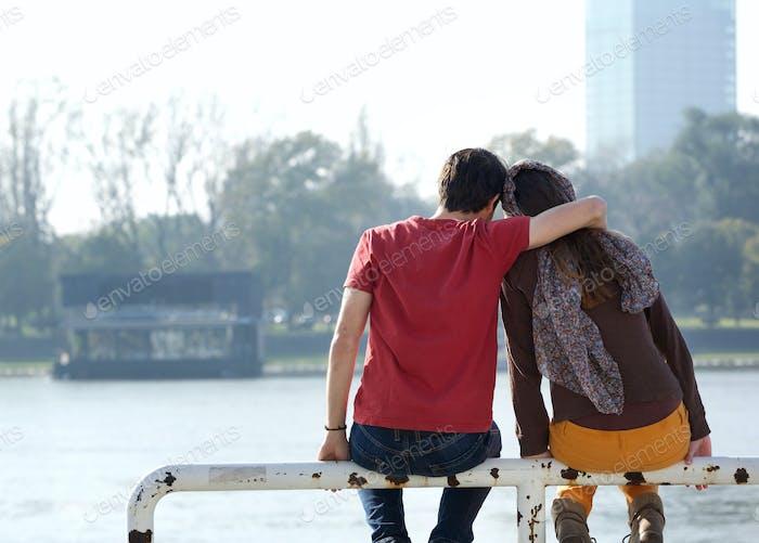 Boyfriend and girlfriend sitting outdoors