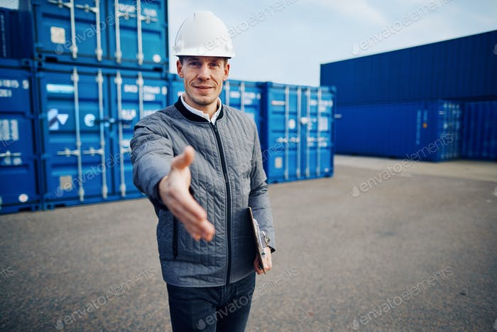 Smiling freight foreman wearing a hardhat shaking hands