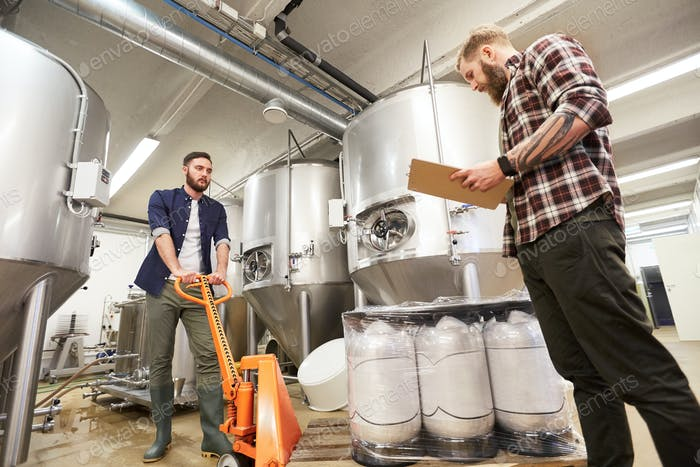 men with beer kegs and clipboard at craft brewery