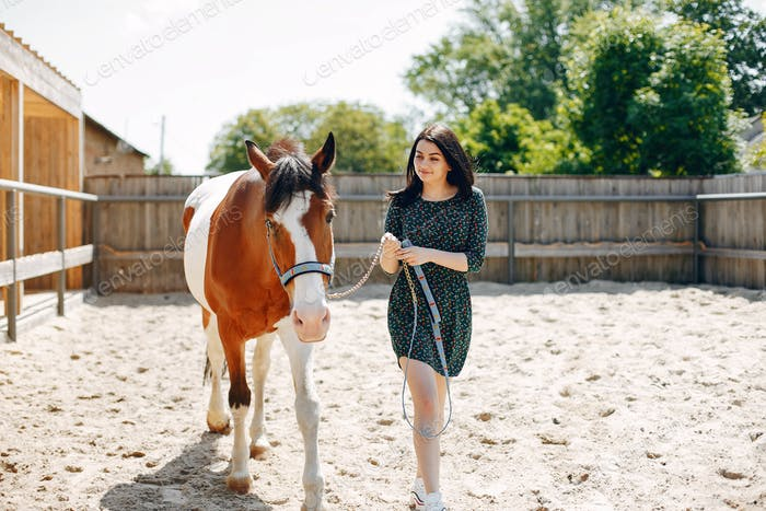 Beautiful woman standing with a horse