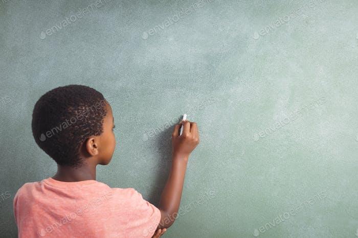 Junge Schrift mit Kreide auf Greenboard in der Schule
