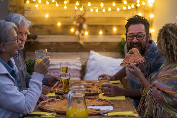 group of adults together on the wooden table eating two big pizzas at the christmas night