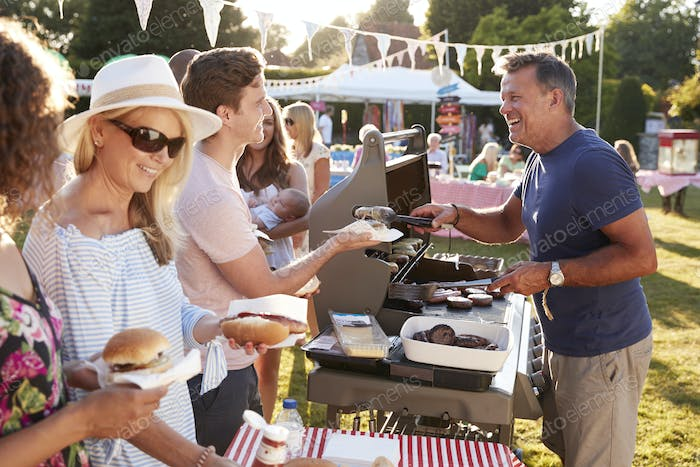Mann Serving auf Barbeque Stall bei Summer Garden Fete