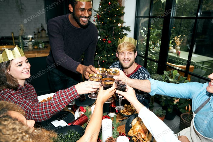 Retro Style Shot Of Group Of Friends Making A Toast Enjoying Christmas Party At Home Together