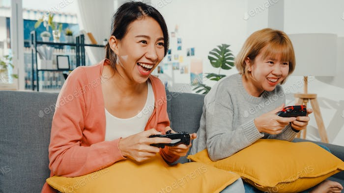 Lesbian LGBTQ women couple play video game at home.