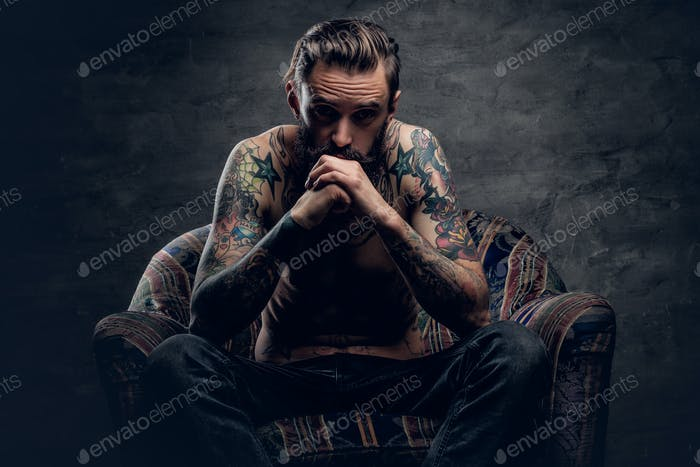 bearded male with naked tattooed torso.
