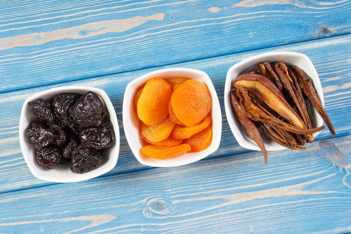 Dried fruits in white bowl on wooden boards, healthy nutrition