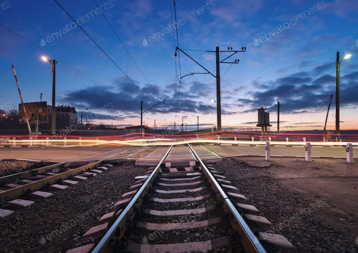 Rail crossing with blurred car lights at beautiful sunset. Railw