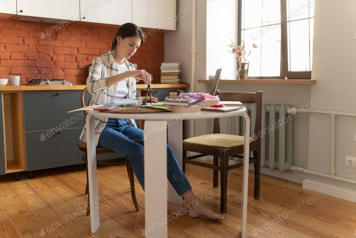 Young woman preparing for exam in kitchen