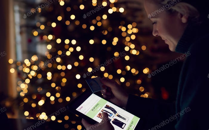 Woman At Home With Credit Card Using Digital Tablet To Shop For Clothes Online At Christmas
