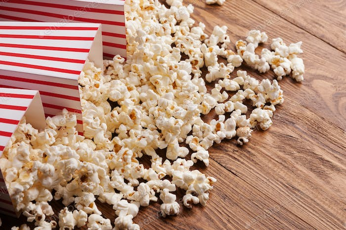 Bucket of popcorn on wooden background