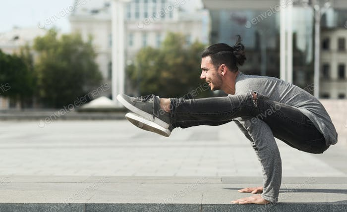 Experienced yoga man doing advanced pose outdoors
