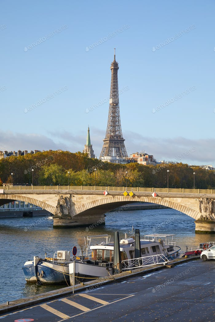 Eiffel tower and Seine river with boats in a sunny day in Paris, France
