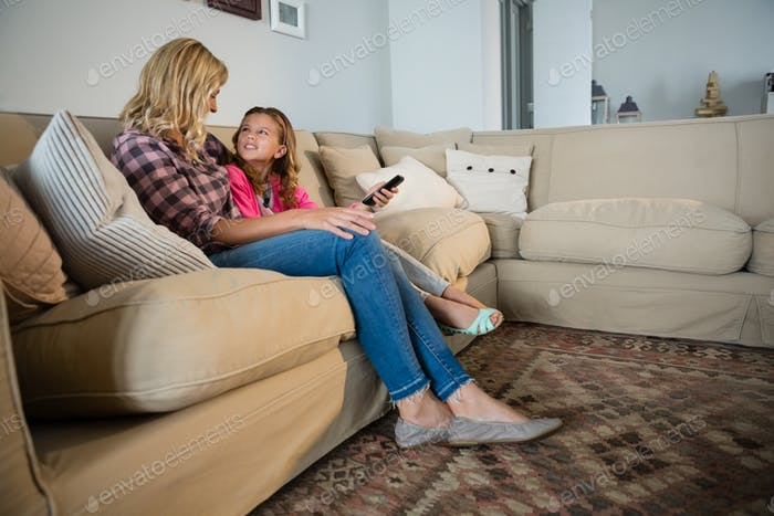 Mother and daughter watching television in the living room