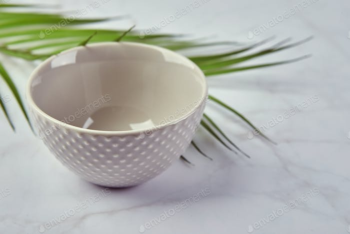 Modern trendy bowl on marble background. Minimalistic composition with tableware.