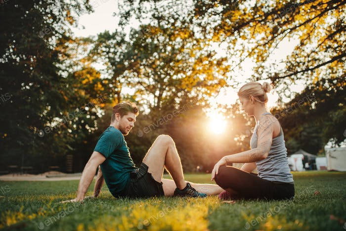 Man and woman exercising at park in morning