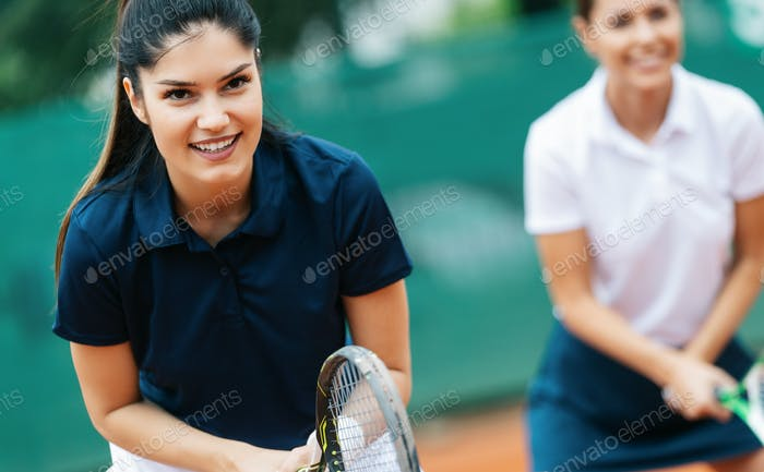 Young happy fit women playing tennis on tennis court