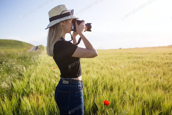 Beautiful young woman with digital camera taking photos in a fie