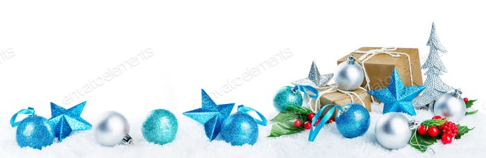 Christmas lantern with gifts, colored balls and stars on snow is