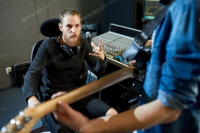 Sound producer talking to musician in studio