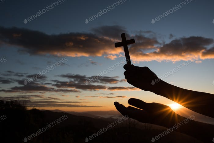Silhouette of Hand hold cross of God