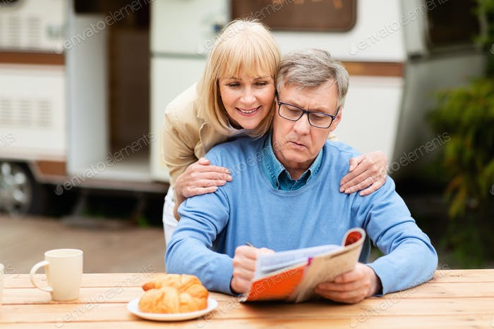Mature woman helping her husband solve crossword puzzle near trailer outdoors