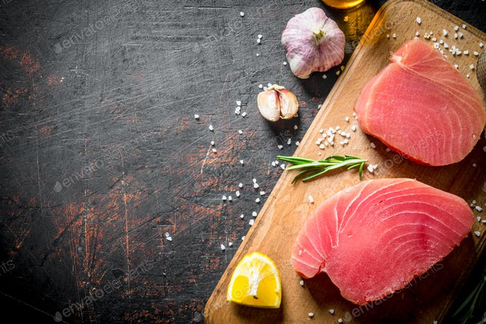 Fresh raw tuna on a cutting Board with lemon and garlic.