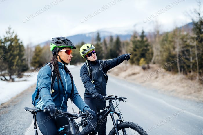 Two mountain bikers riding on road outdoors in winter