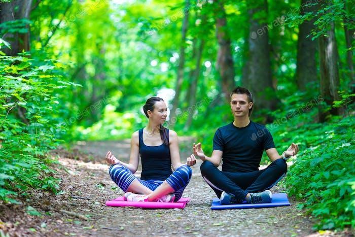 Young active couple making stretching yoga exercises outside in park