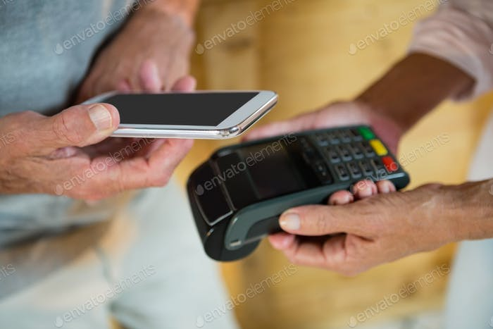 Customer making payment through NFC technology on mobile phone