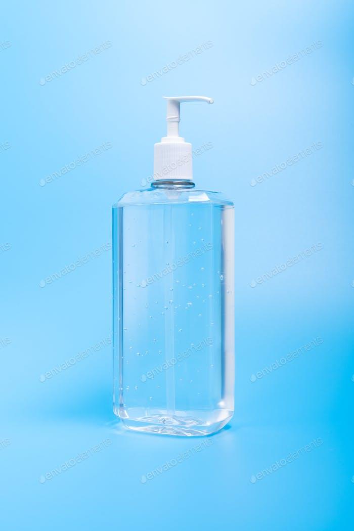 Hand sanitizer in plastic bottle on blue background