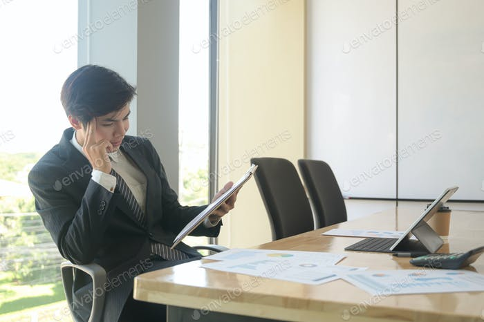 oung executives are checking company earnings. He uses tablet and check the data from chart.