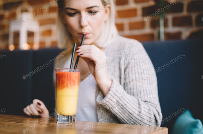 Young woman sipping a healthy smoothie in a restaurant.