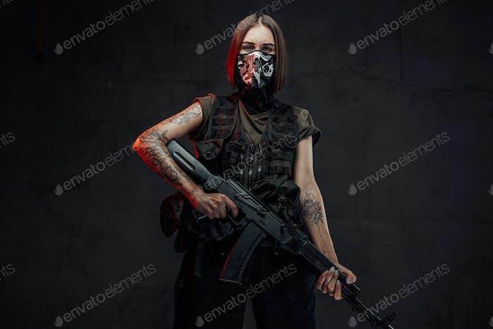 Llevado con máscara mercenario hembra sosteniendo rifle