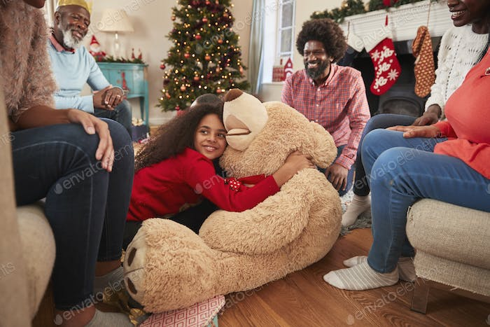 Children Playing With Giant Teddy Bear As Multi-Generation Family Open Gifts On Christmas Day