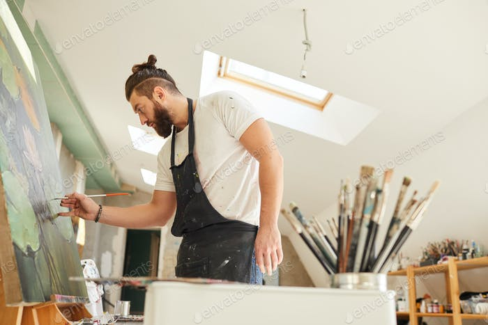 Bearded Male Artist Painting on Easel