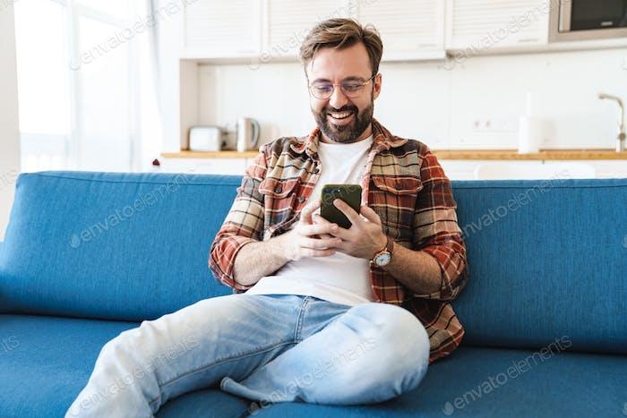 Retrato de joven sonriendo y el uso del teléfono móvil en el sofá en casa