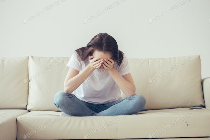 A girl in despair cover  face with her hands sitting on a beige sofa. Beautiful girl close face