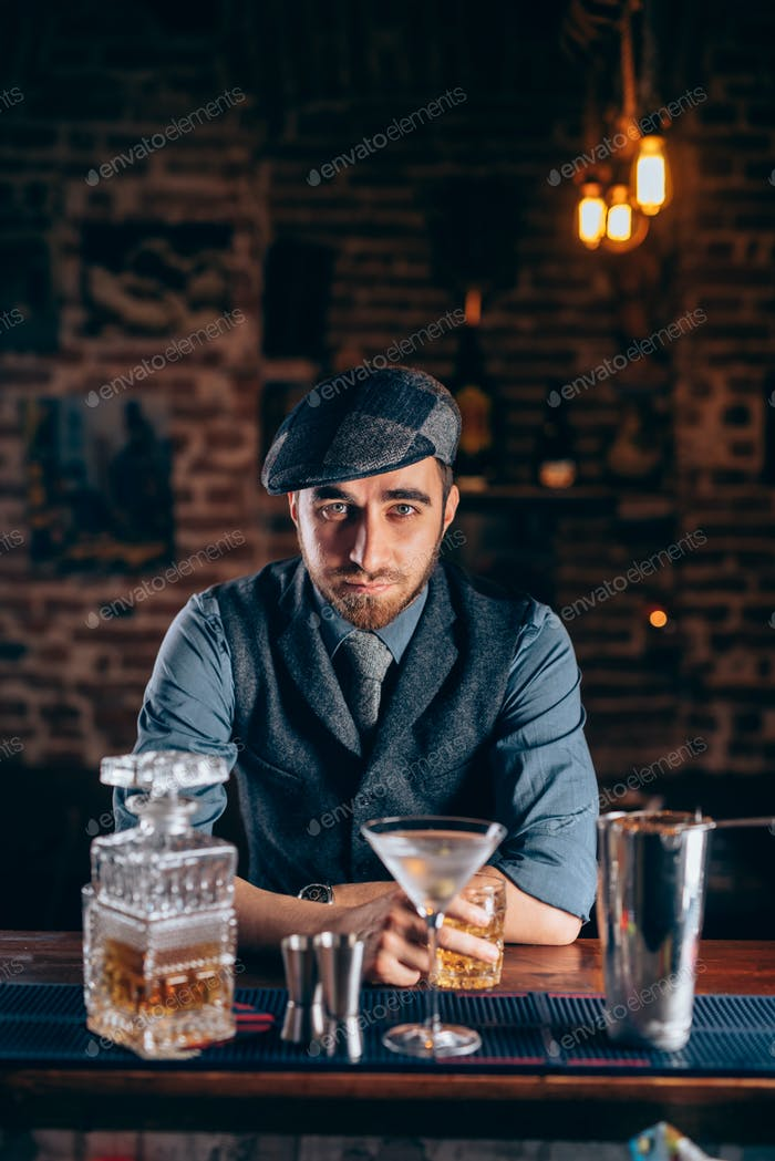 Vintage man enjoying a relaxing old fashioned drink at bar.
