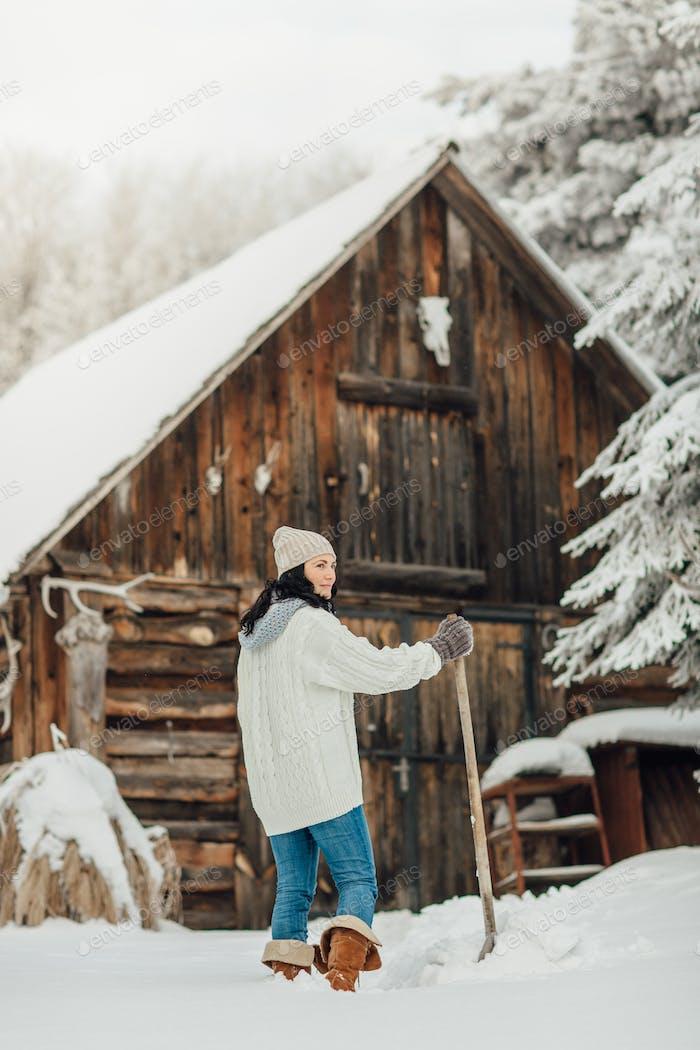 Portrait of a woman shoveling snow