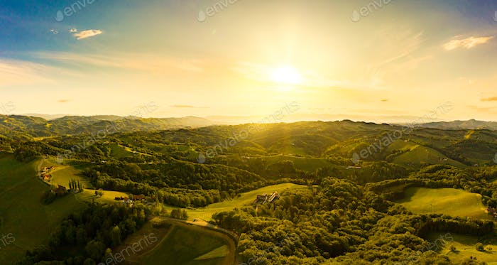 Gorgeous sunset over beautiful green vineyards. Aerial panorama sunset over Austrian grape hills in