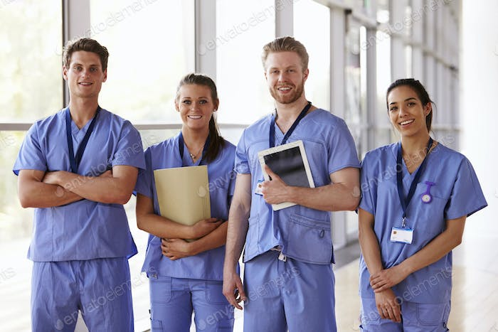 Group portrait of healthcare workers in hospital corridor