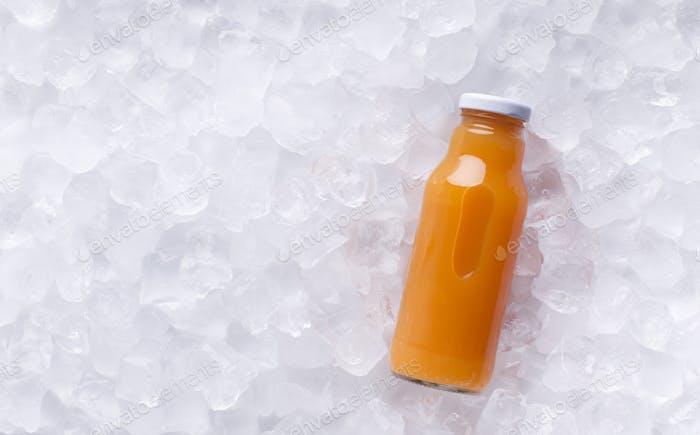 Zumo de desintoxicación de naranja en botella de vidrio sobre Fondo de cubitos de Hielo
