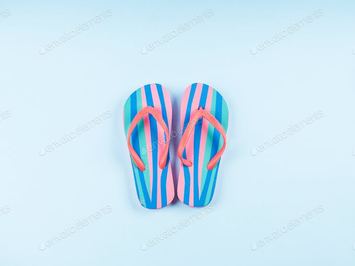 Summer flip flop pair on blue background