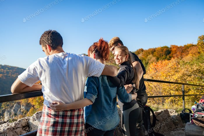 Group of happy people looking at beautiful landscape on the peak of the mount