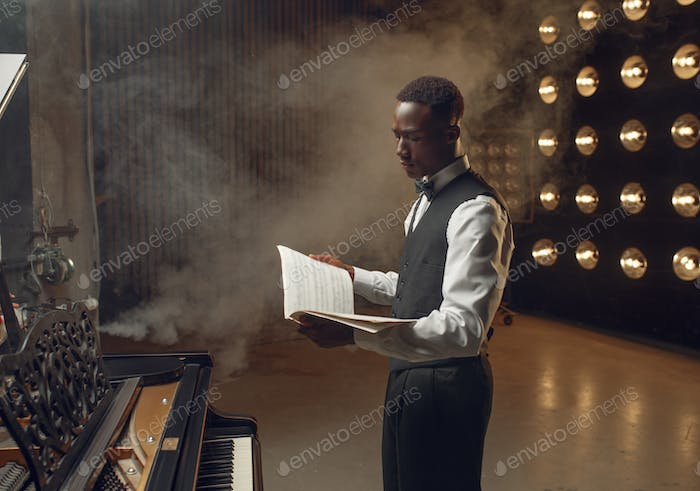 Ebony pianist with music notebook on the stage